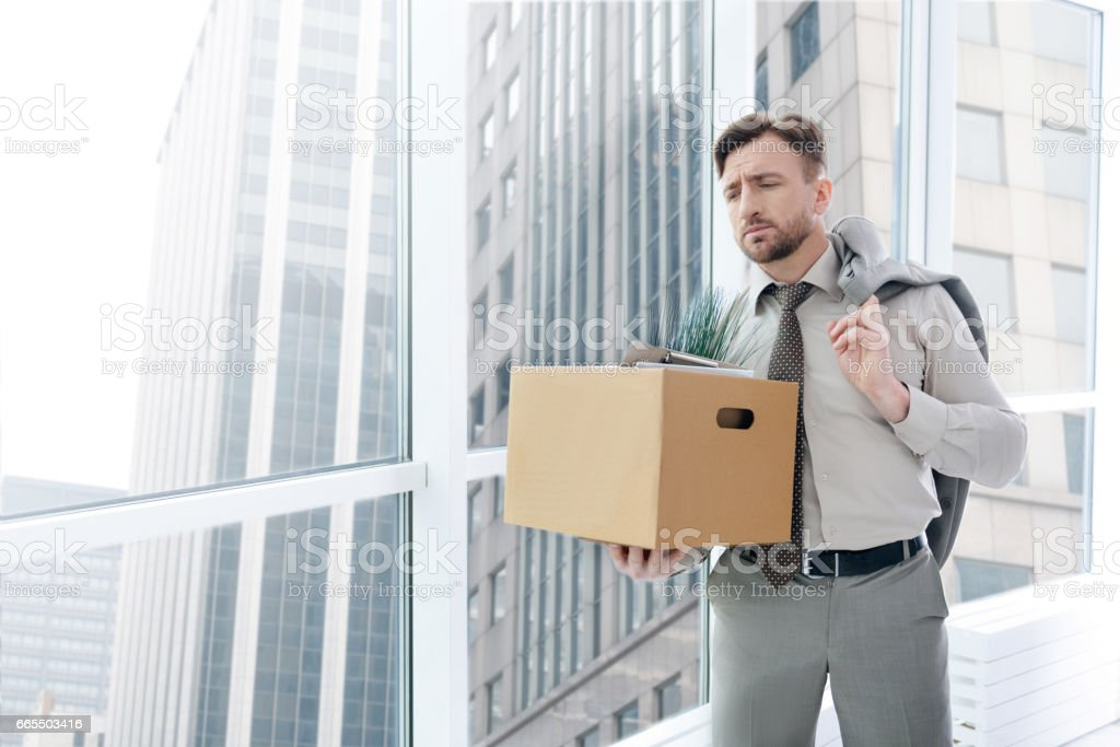 Fired gloomy man standing in the office stock photo