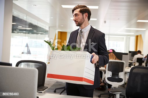 1181817161 istock photo Fired male employee holding box of belongings in an office 869286460