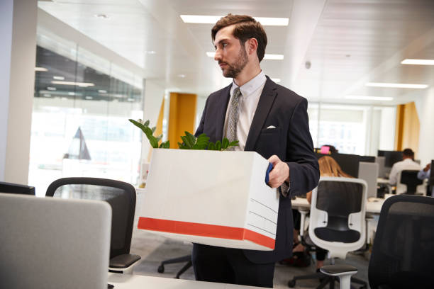 Fired male employee holding box of belongings in an office stock photo