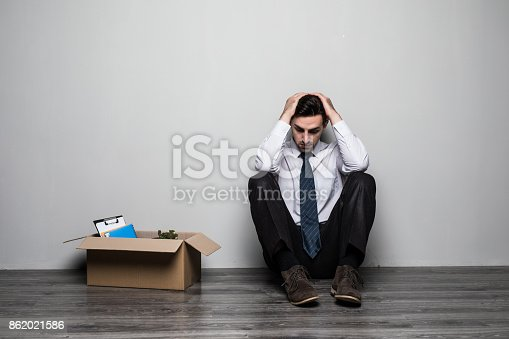 1181817161 istock photo Fired sad frustrated man in suit sitting near office. 862021586