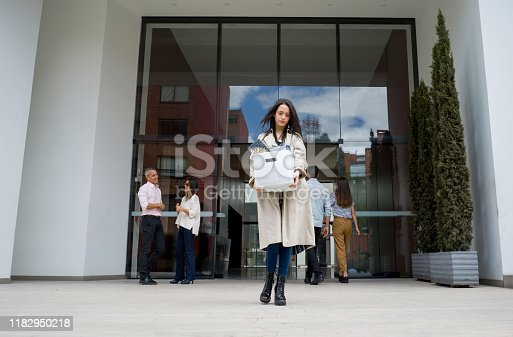 Fired woman leaving the office building with her belongings in a box and looking sad - losing a job concepts