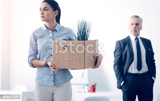 1181817161 istock photo Fired young brunette with box full of stuff leaving office 868057684
