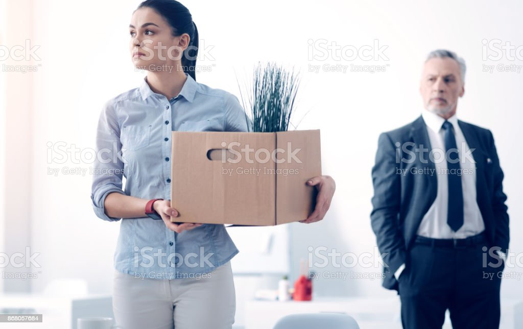 Fired young brunette with box full of stuff leaving office stock photo
