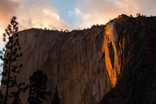 A February evening, the sun shines on Horsetail Fall on the edge of El Capitan in Yosemite Valley where the
