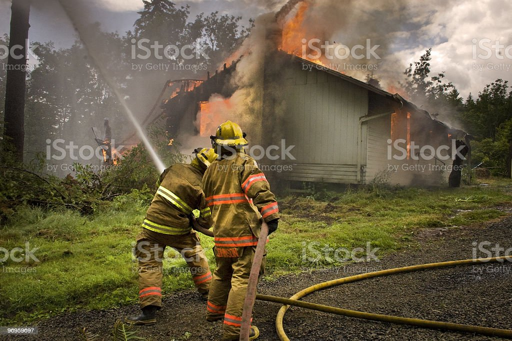 Firefighers and housefire stock photo