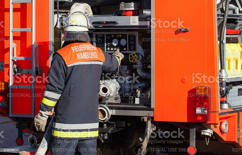Firefighter activates the fire water supply to the emergency vehicle stock photo