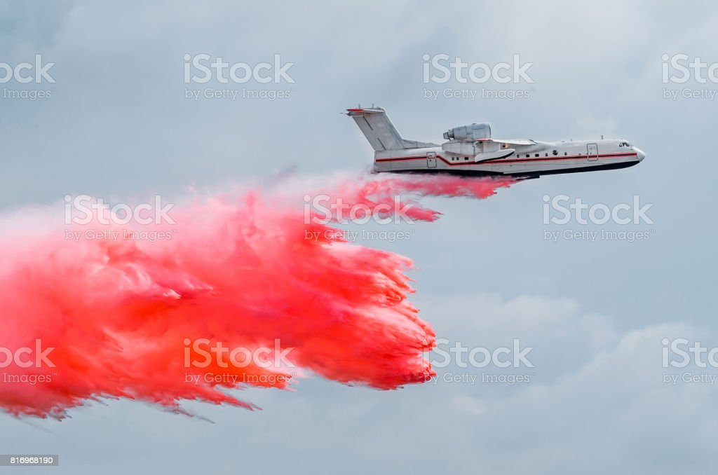 Firefighter airplane drops red water on a fire in the forest stock photo