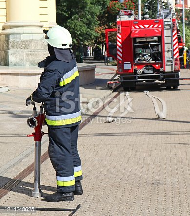 Firefighter and a firetruck on the street