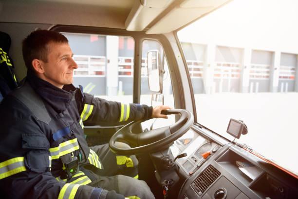 feuerwehrmann am steuer einen rettungswagen fährt zum ort des geschehens und löscht feuer - feuerwehrmann deutsch stock-fotos und bilder