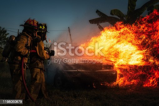 Firefighter attempt to extinguish a fire on a burning car Gas-powered vehicles.