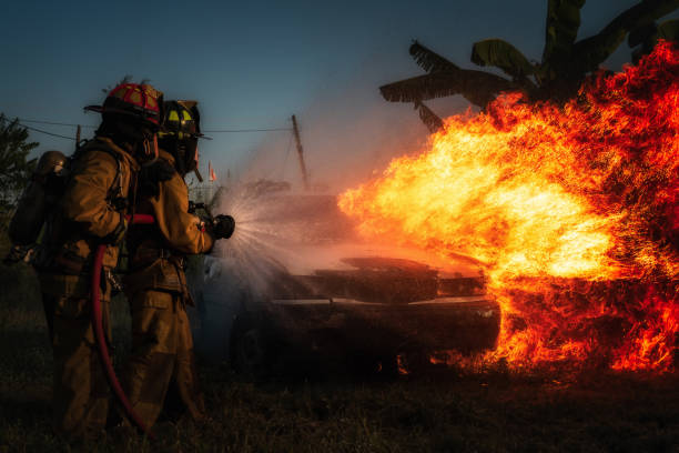 Firefighter attempt to extinguish car. stock photo