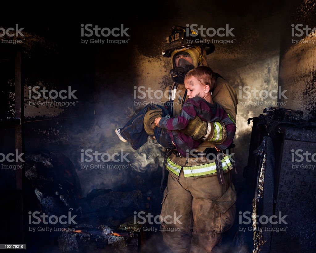 Firefighter Carrying Boy stock photo