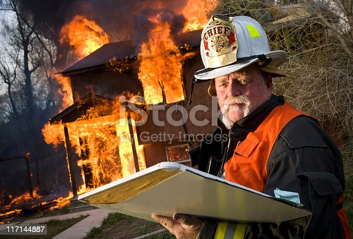 A firefighter chief stands before a residential structure fire holding an accountability chart with copy-space.