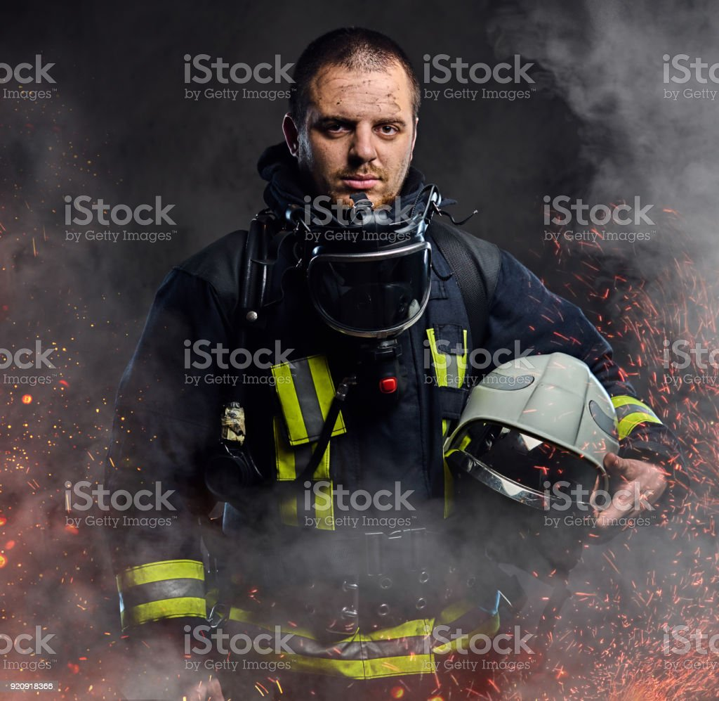 A firefighter dressed in a uniform in a studio. stock photo