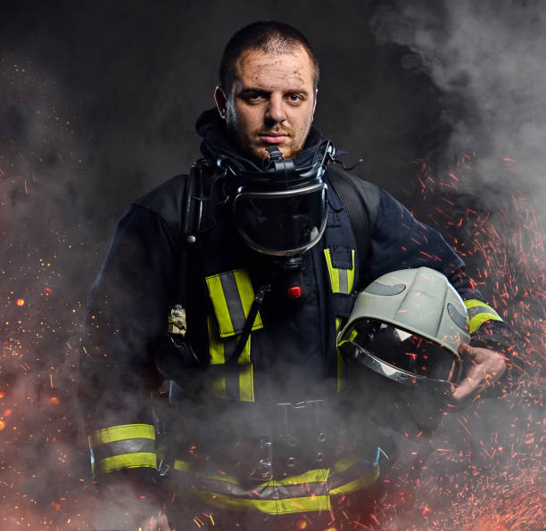 un bombero vestido con un uniforme en un estudio. - bombero fotografías e imágenes de stock