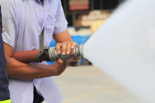 Bombero lucha contra usar la manguera de agua en un simulacro de incendio. - foto de stock