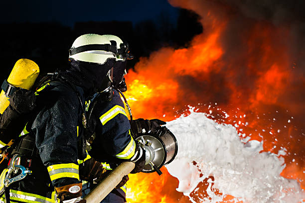Firefighter - Firemen extinguishing a large blaze Firefighter - Firemen extinguishing a large blaze extinguishing stock pictures, royalty-free photos & images