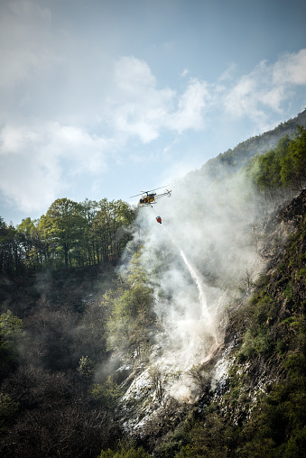Firefighter helicopter putting out a fire on mountain forest