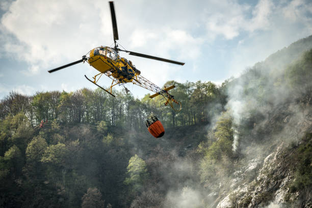 Firefighter helicopter putting out a fire on mountain forest Firefighter helicopter putting out a fire on mountain forest environmental damage stock pictures, royalty-free photos & images