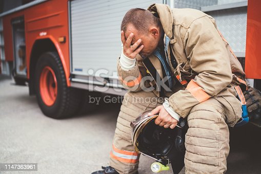 Unhappy firefighter sitting at the fire engine