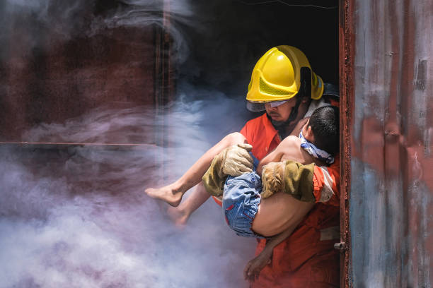 Firefighter holding child boy to save him in fire and smoke,Firemen rescue the boys from fire