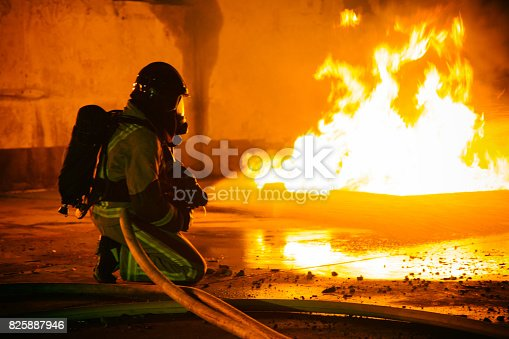 Firefighter in uniform spraying water against smoke at night.