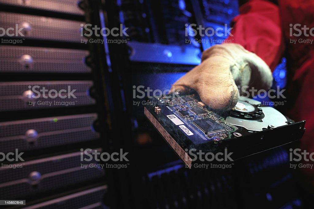 Firefighter holding smoking computer hard drive stock photo