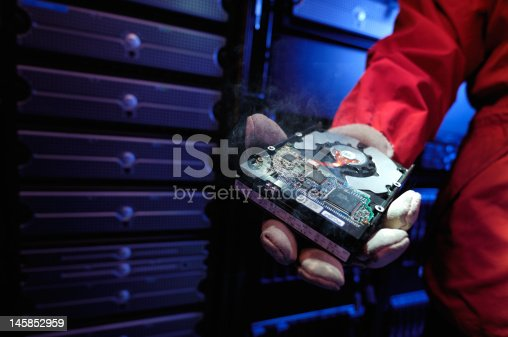 Firefighter hand holding smoking computer hard drive in data center