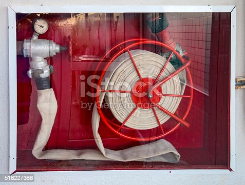 Firefighter hose on the red background behind a glassdoor with fain reflection of the room