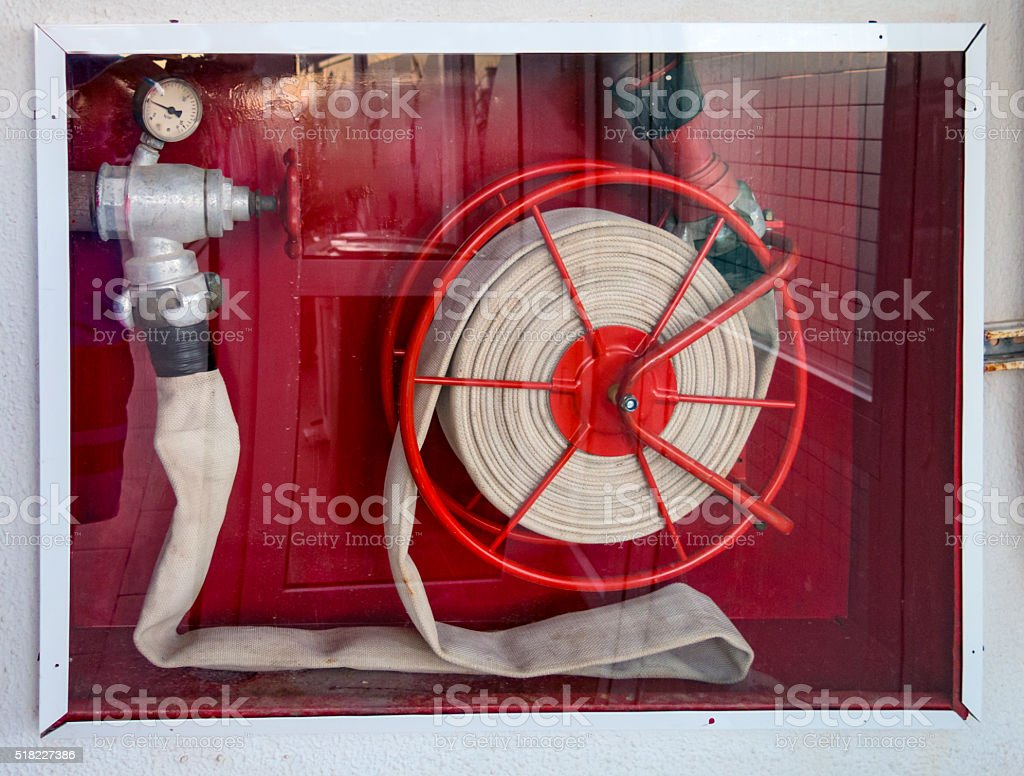 Firefighter hose on the red background in a glassdoor stock photo