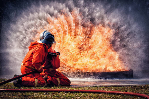 Firefighter in fire fighting suit spraying water, Firemen fighting  raging fire with huge flames of burning, Fire prevention and extinguishing concept Firefighter in fire fighting suit spraying water, Firemen fighting  raging fire with huge flames of burning, Fire prevention and extinguishing concept extinguishing stock pictures, royalty-free photos & images