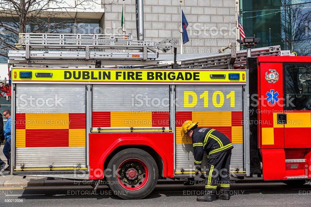 Bombero en frente de un camión de bomberos. - foto de stock