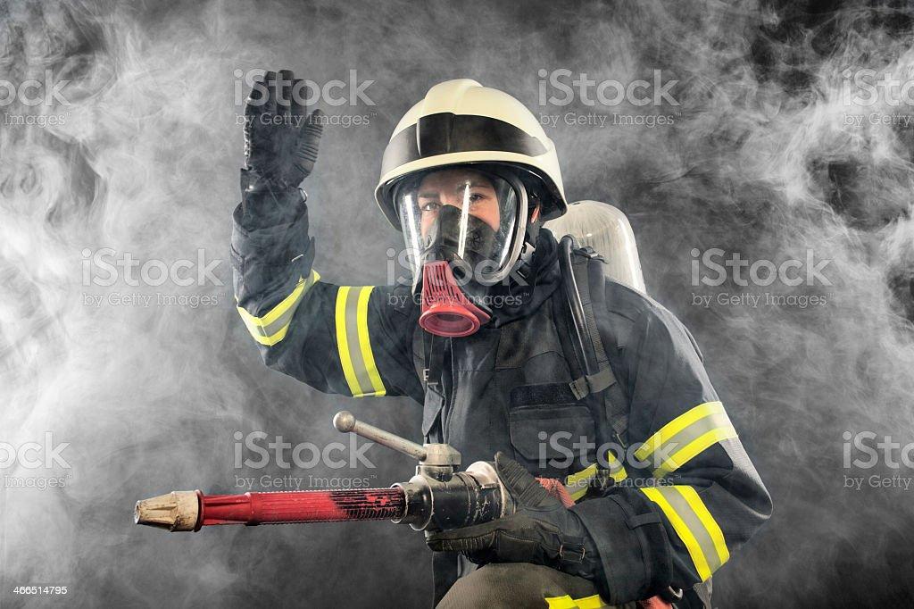 Firefighter in full gear battling smoke stock photo