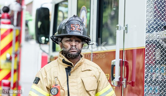 A fireman standing outside his fire truck, wearing his fire protection suit and helmet. He is a young African-American man in his 20s. He is looking at the camera with a serious expression.