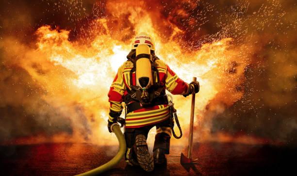 A firefighter kneels before the fire Ein Feuerwehrmann steht vor einer großen Aufgabe. Er ist mit schwerem Atemschutz ausgerüstet und trägt eine Schutzausrüstung, die ihn vor der Hitze und den Flammen schützt. extinguishing stock pictures, royalty-free photos & images