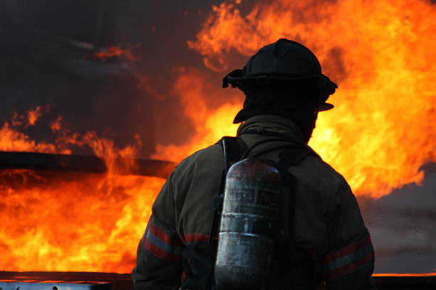 Firefighter looking at flames stock photo