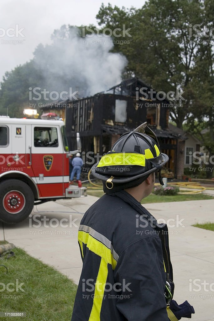 Firefighter observing burned house royalty-free stock photo