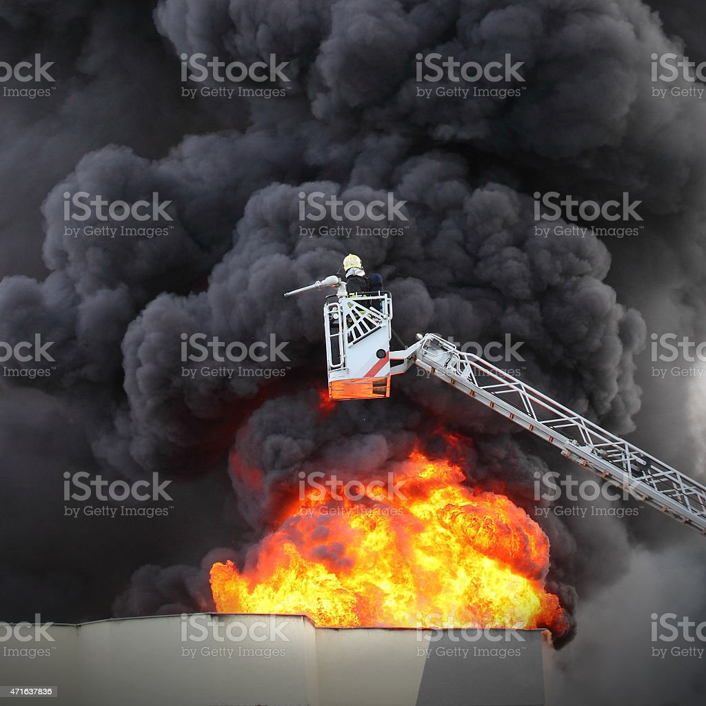 Firefighter on lift attempting to extinguish a factory fire stock photo