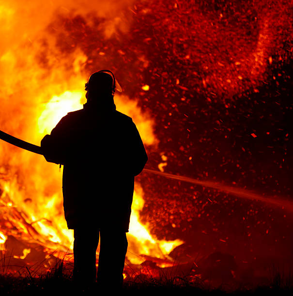 firefighter silouette of a firefighter against large fire in the dark smoke jumper stock pictures, royalty-free photos & images