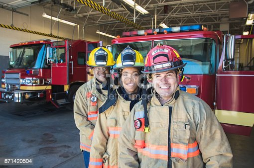 A stock group/team of firefighters looking into the camera.