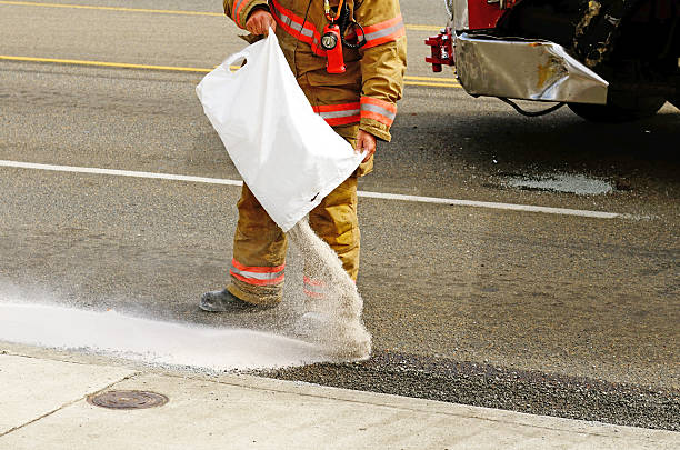 Firefighter pouring absorb any on oil spilled from a wreck Fire fighers spreading absorbant at a four vehicle accident involving two large trucks resulted in a single injury and a diesel fuel spill. July 17, 2012 in Roseburg Oregon porous stock pictures, royalty-free photos & images
