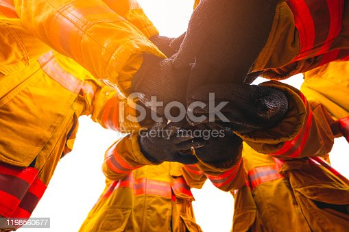 istock Firefighter putting hands up for fire fighting, Cheerful people giving strength motivation. Teamwork concept 1198560677