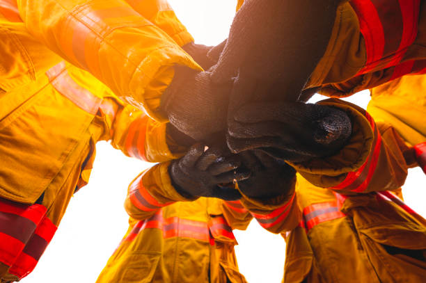 Firefighter putting hands up for fire fighting, Cheerful people giving strength motivation. Teamwork concept stock photo