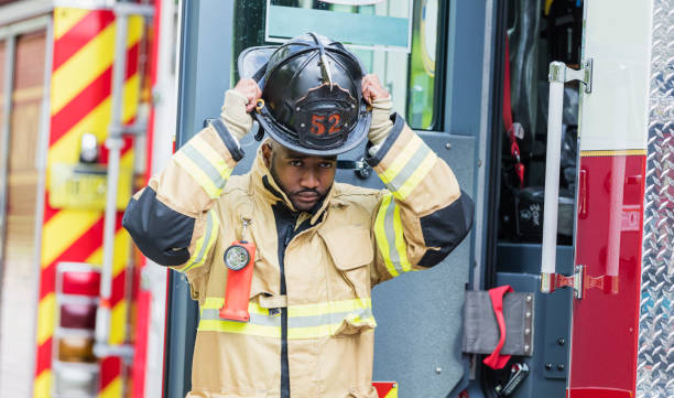 Firefighter putting on fire protection suit and helmet stock photo