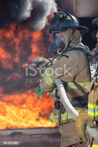 Firefighter ready to spray water.  This stock image has a vertical composition.