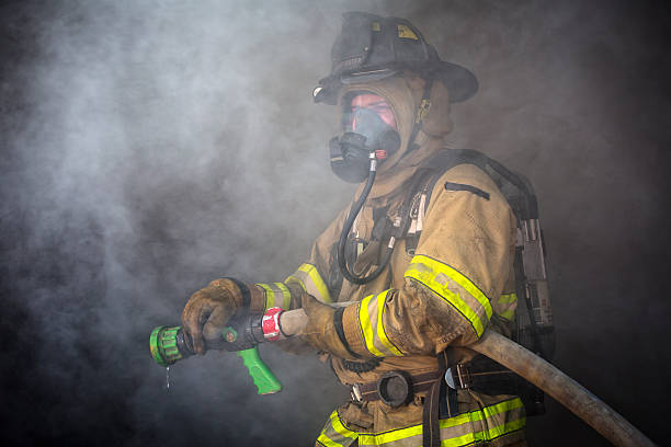 Firefighter ready to spray water Firefighter ready to spray water.  This stock image has a horizontal composition. smoke jumper stock pictures, royalty-free photos & images