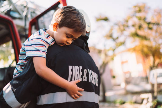Firefighter rescue operation Firefighter carrying little boy after successful rescue operation salvation stock pictures, royalty-free photos & images