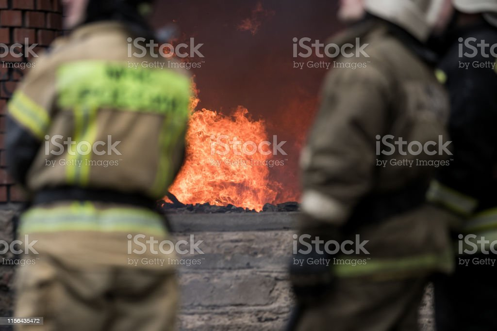 Firefighter rescue working from burning building in fire and smoke...