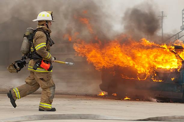 Firefighter running toward burning building