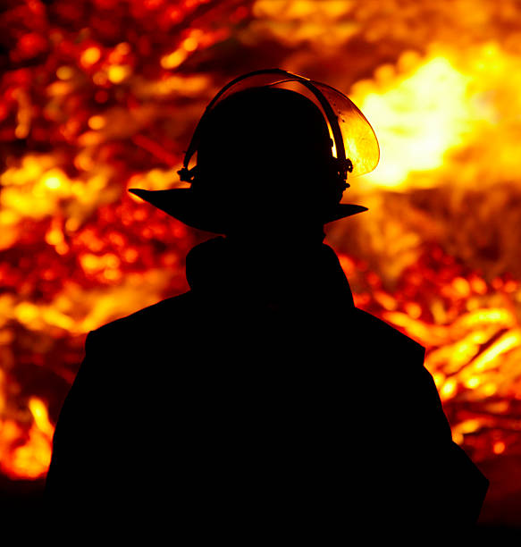 Firefighter silhouette against glowing fire silouette of a firefighter against large fire in the dark, soft fokus smoke jumper stock pictures, royalty-free photos & images